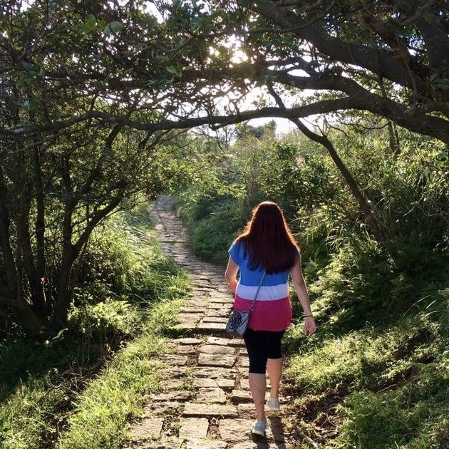 image of a lady with long brown hair walking down a path