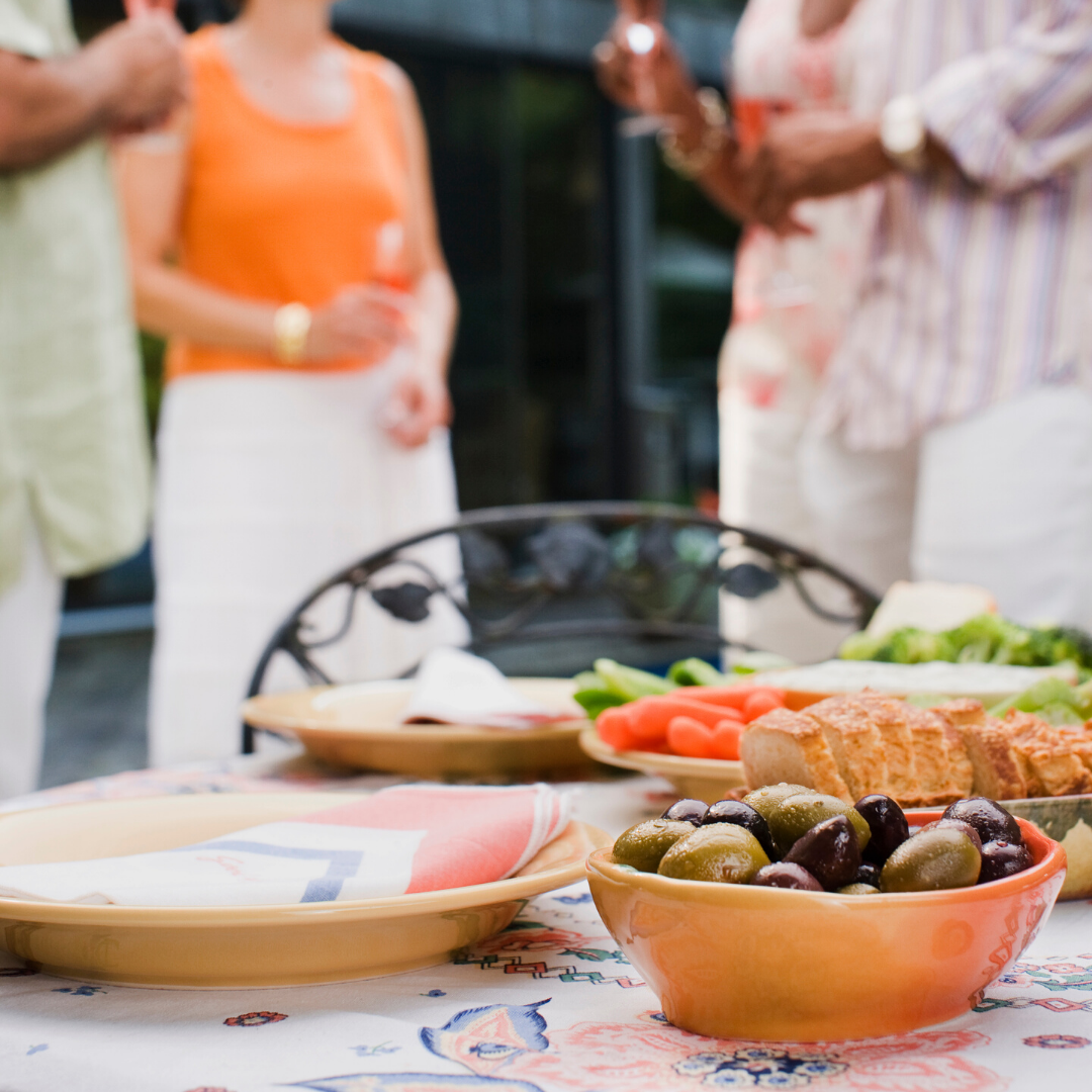 Food in platters on a table with people in the background gathered in a group of three