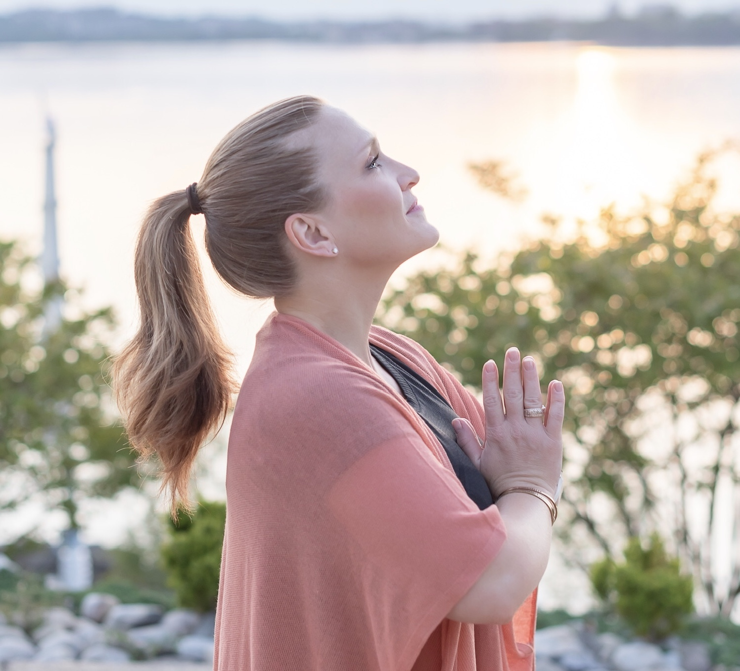 side view of a redhead with a ponytail, hands in pray, and looking up