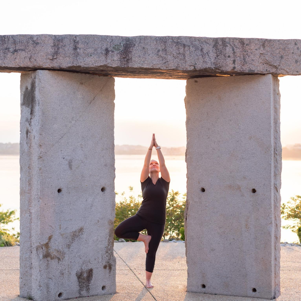 Woman in between two pillars in the tree pose