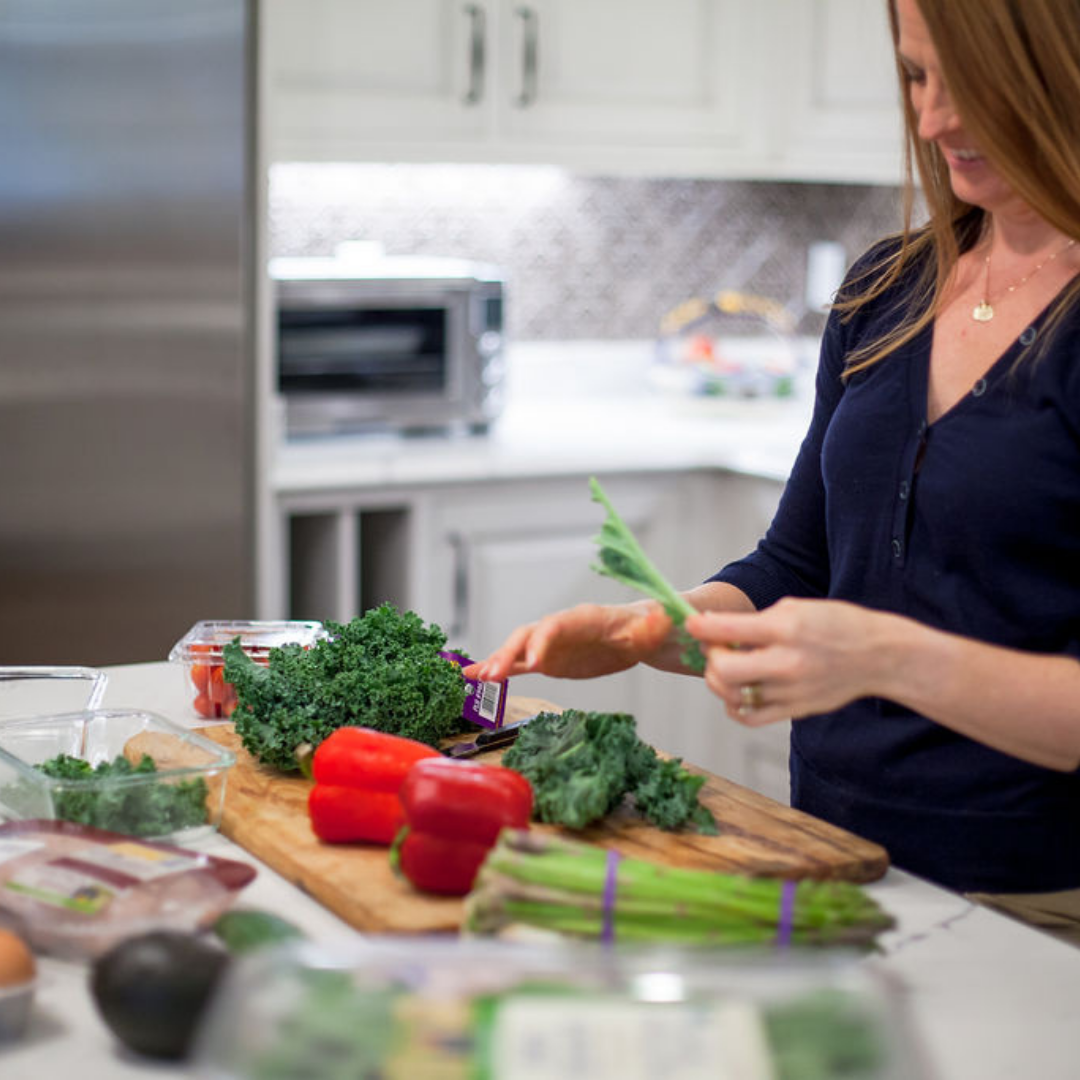 woman holding lettuce with vegetables on counter
