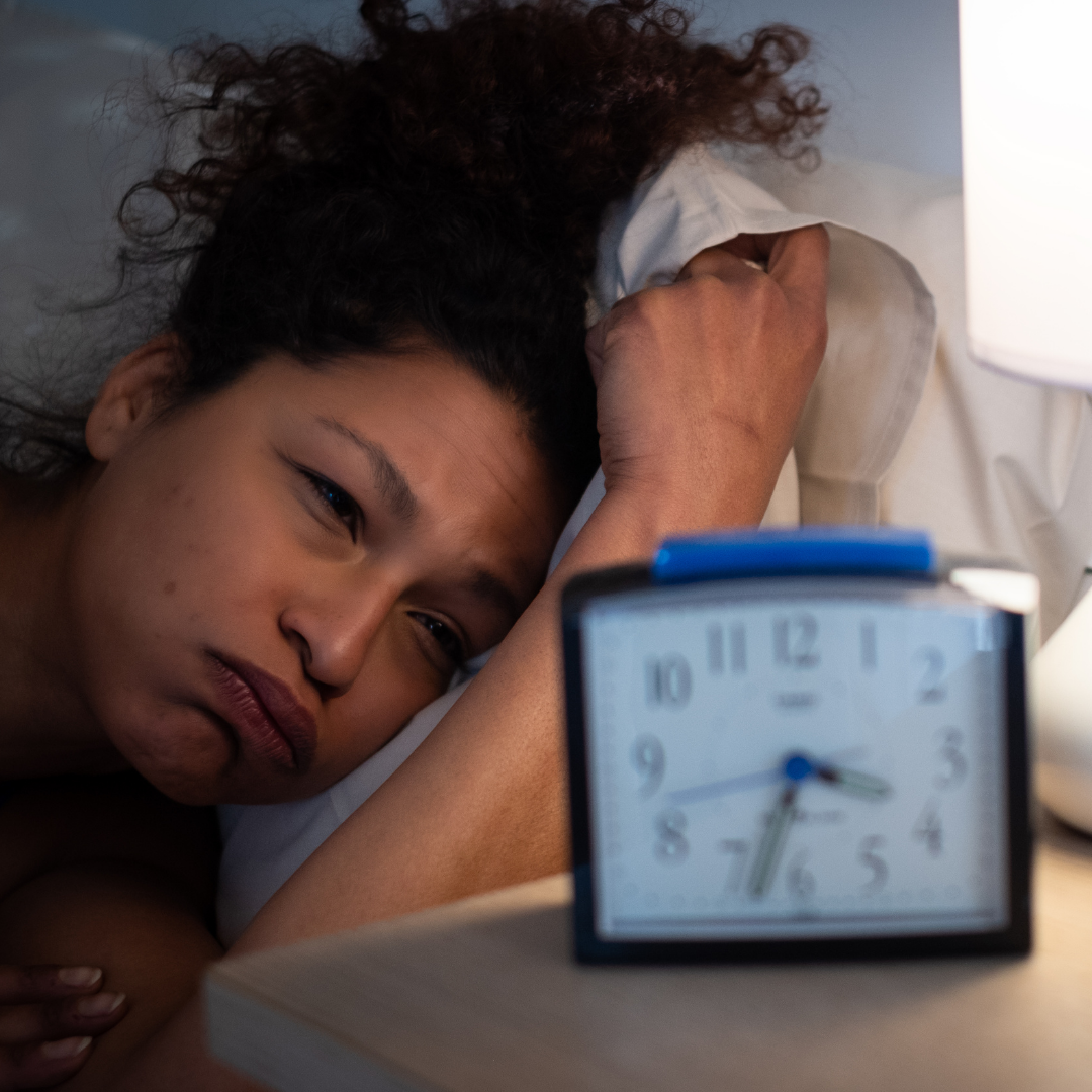 lady laying in bed, next to a clock reading 3:33am, frustrated she can't sleep