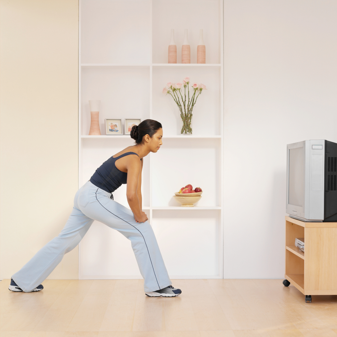 a lady in workout clothes lunging forward looking at a TV