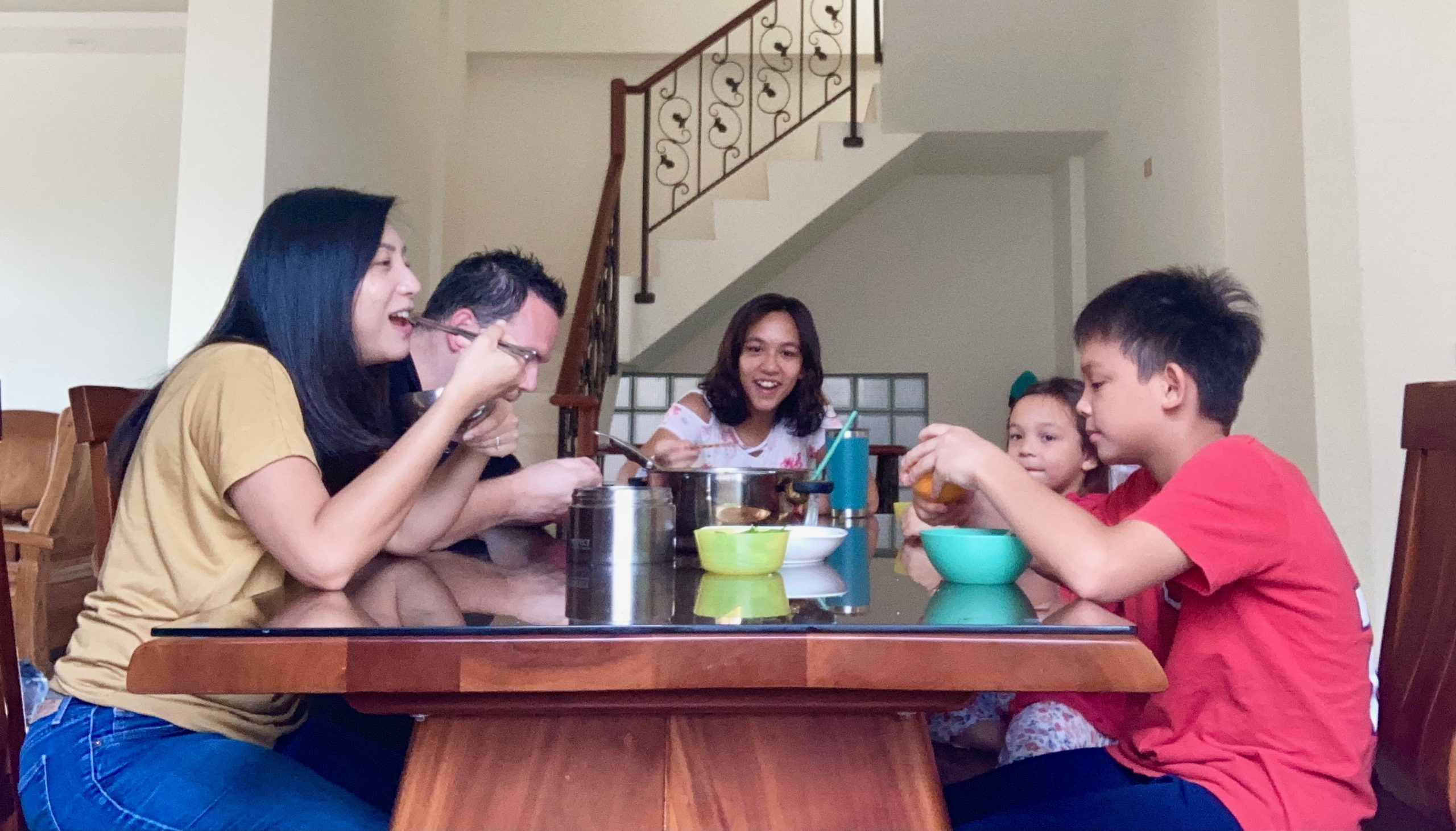 Family of 5 sitting around a table eating