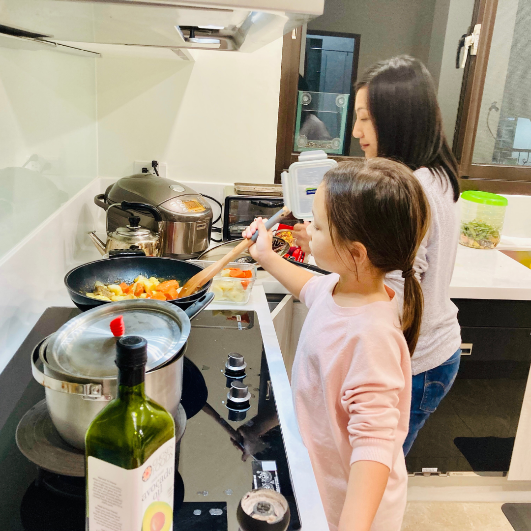 mom and young daughter cooking together