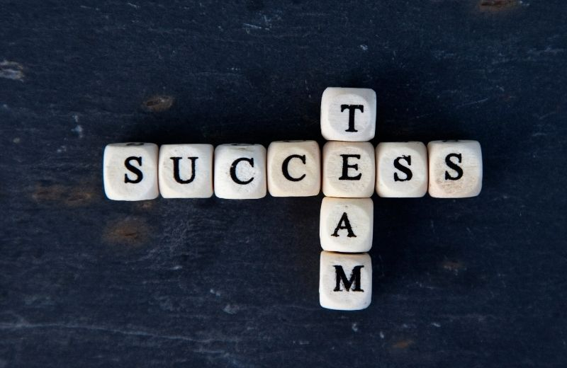 Team and success spelled with letter dice