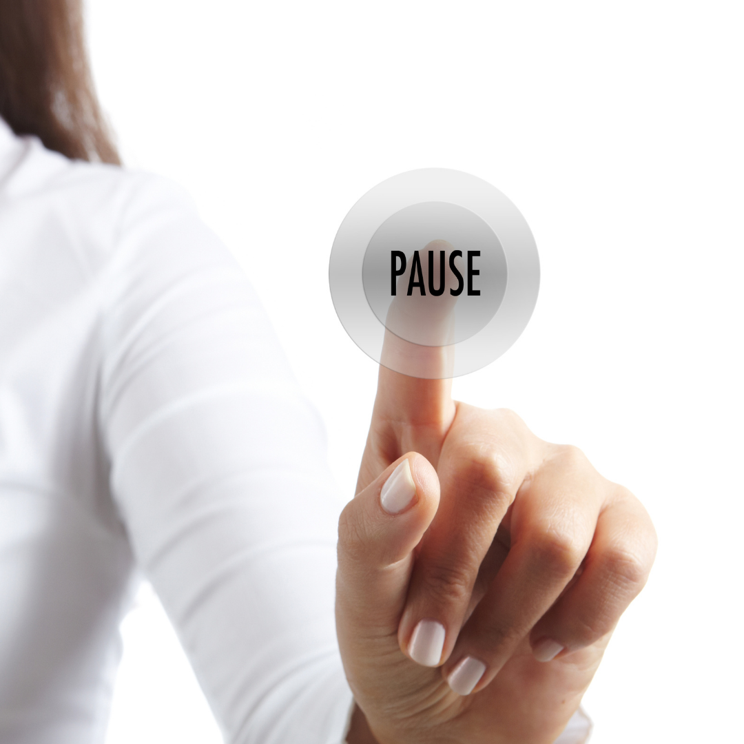 """A lady pushing a button that reads """"pause"""""""