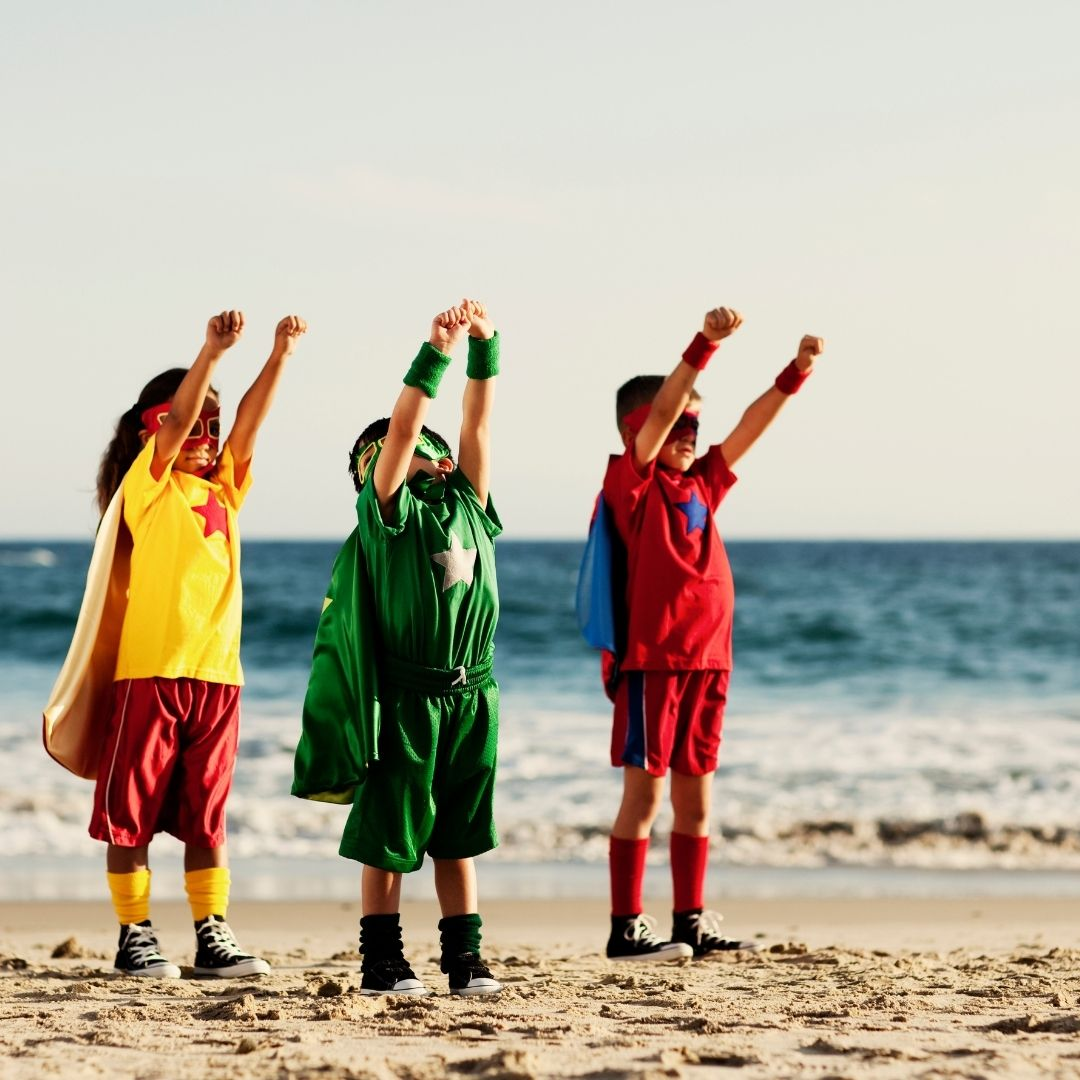 3 kids in hero costume and capes standing with arms up in the air as if they are about to take off