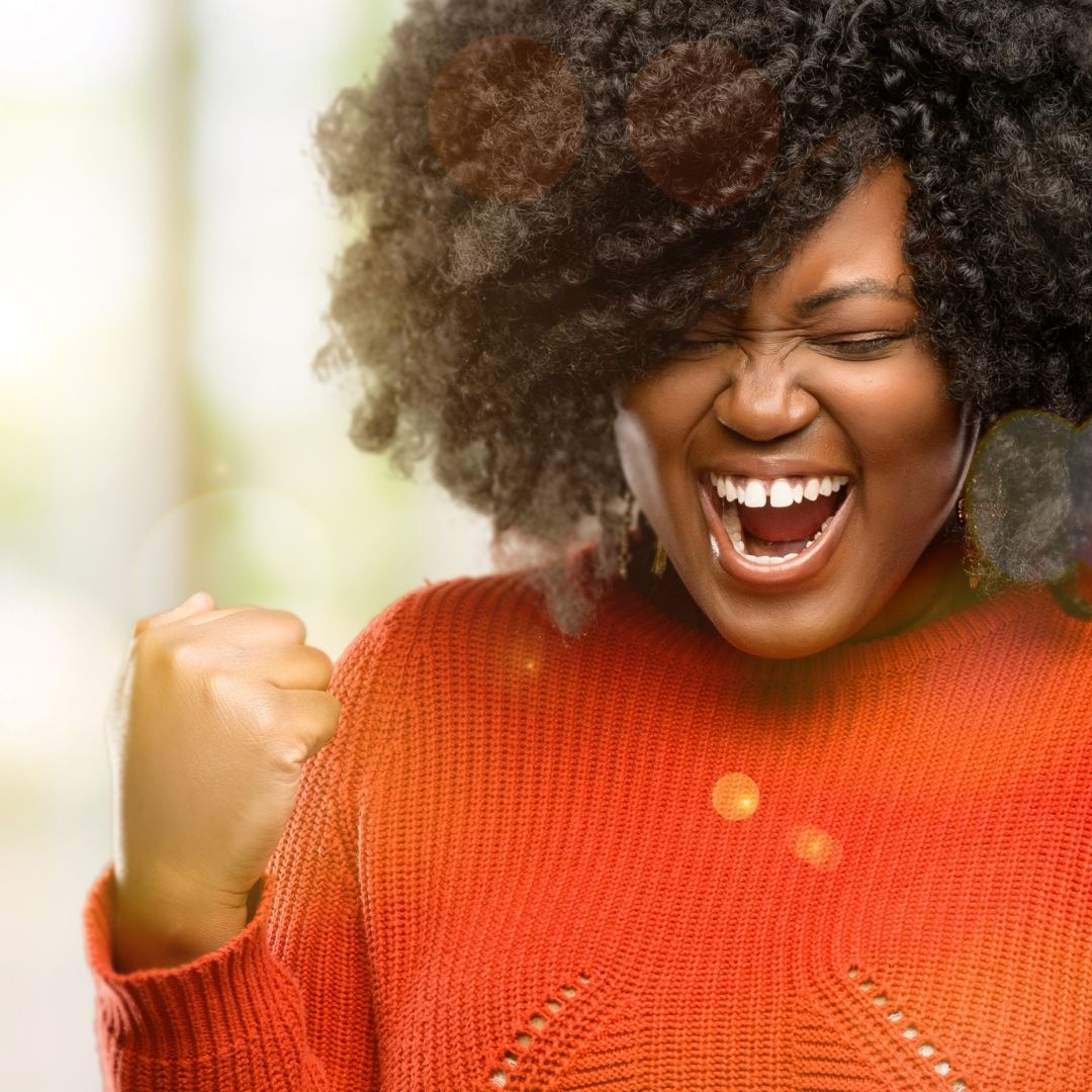 lady in an orange sweater with an expression that she has achieved or won something