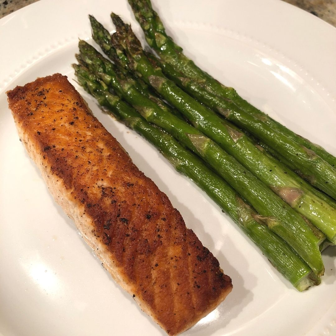 White plate with a piece of pan-seared salmon and stack of roasted asparagus