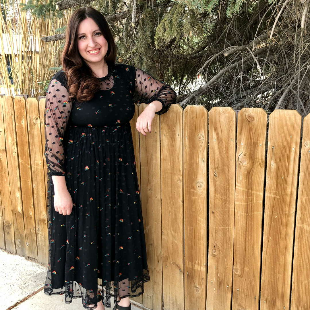 Lady with long dark hair standing by a fence in a black dress with flowers