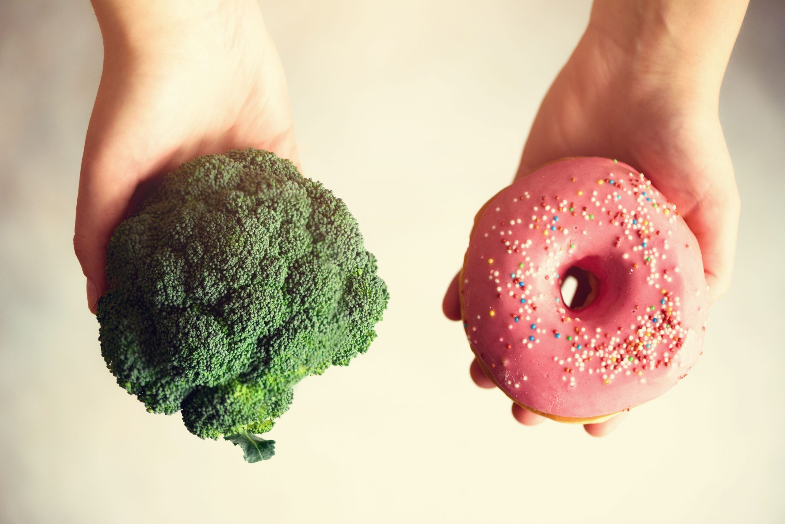 One had holding a broccoli crown. Another hand holding a donut with pink icing and sprinkles