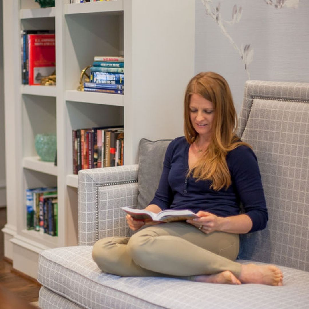 A long read headed lady sitting with leg folding on a couch reading a book.