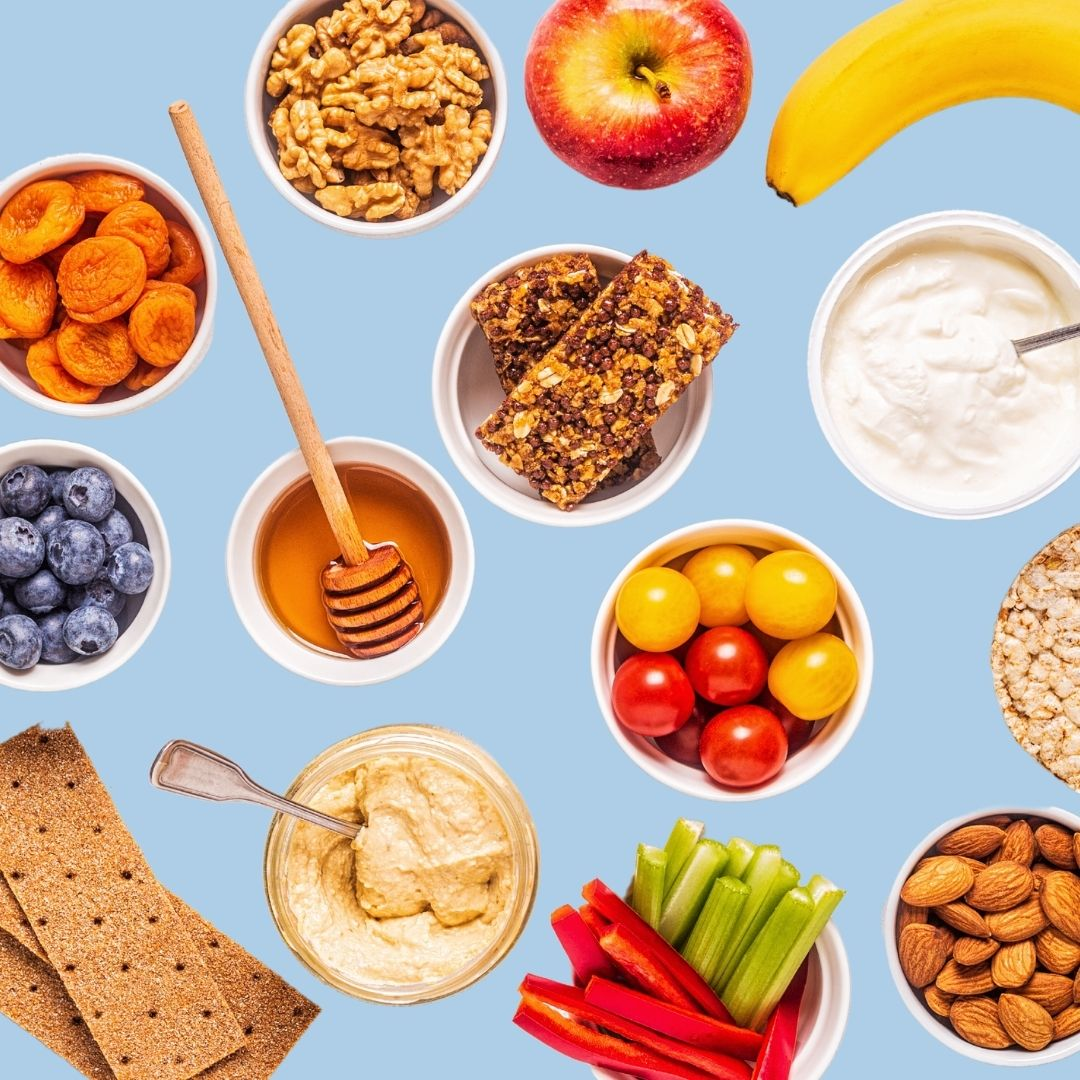 Healthy snacks of apples, bananas, whole wheat crackers, and bowls of almonds, walnuts, tomatoes, bell pepper slices, greek yogurt, blueberries, dried apricots